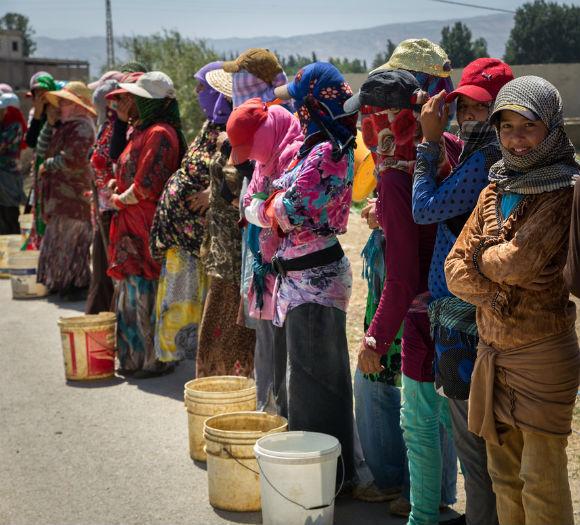 Mujeres refugiadas sirias que viven en un asentamiento informal al lado de una carretera esperan para salir a trabajar a los campos de tomates en el valle de Bekaa en el Líbano.
