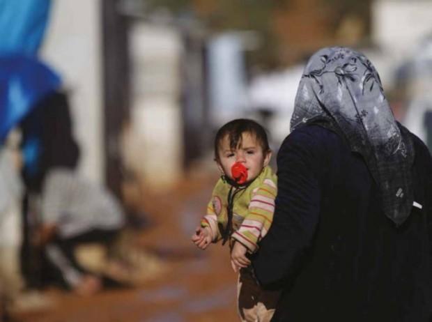 Una mujer camina con su hijo en brazos en un asentamiento de refugiados sirios. Imagen de Khalil Ashawi.