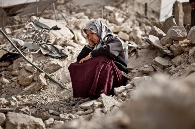 Zakia Abdullah, una mujer siria, sobre los escombros de su vivienda tras la explosión de un misil en Alepo. Imagen de Pablo Tosco/Oxfam Intermón.