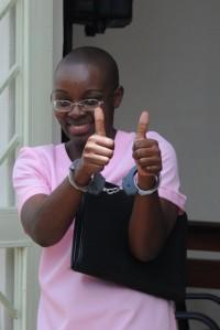 Victoire saluda a sus seguidores durante el juicio, vestida con el uniforme rosa de los presos de Rwanda. Imagen: FDU.