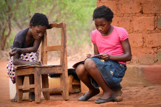 Grace and Georgina escriben sus tareas escolares. Cada día tienen que caminar 50 minutos para buscar agua. Imagen: Kapululwe ADP.