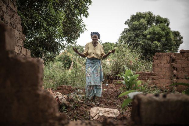 Josephine entre las ruinas de su casa destruida, dónde regresa a limpiar las hierbas ya recoger vegetales silvestres para comer. Huyó cuando quemaron su casa y mataron a sus vecinos. Foto: Pablo Tosco/Oxfam