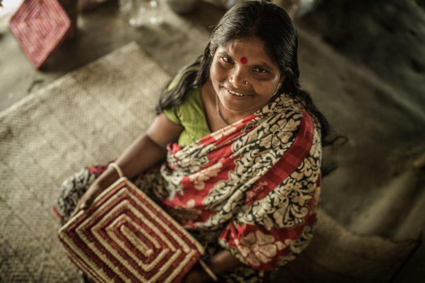 Puspo Biswas muestra una de las cestas elaboradas por ella en la comunidad de Kamarali, en Bangladesh. Imagen de Pablo Tosco/Oxfam Intermón