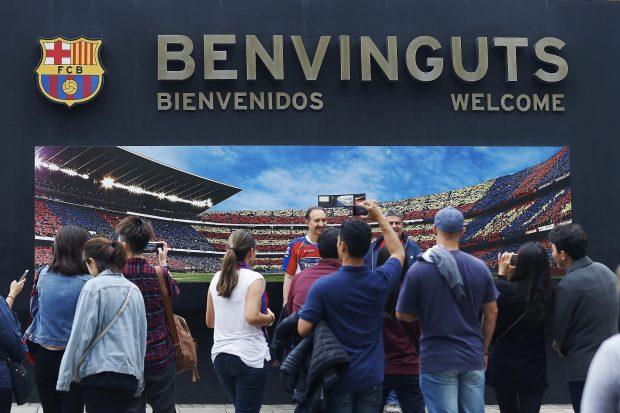 Varios aficionados del Barça se hacen una foto con el mural de la entrada al Camp Nou. (EFE)