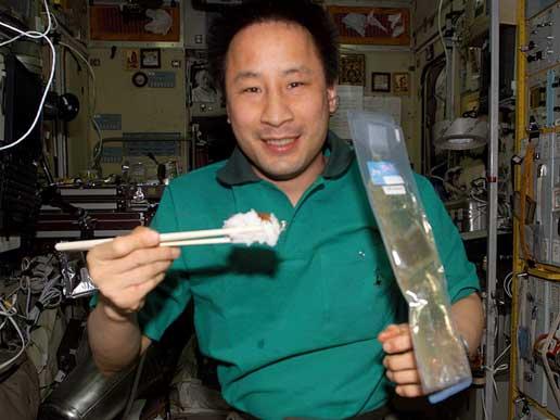 El astronauta Ed Lu, comiendo con palillos en la ISS. Imagen de NASA.