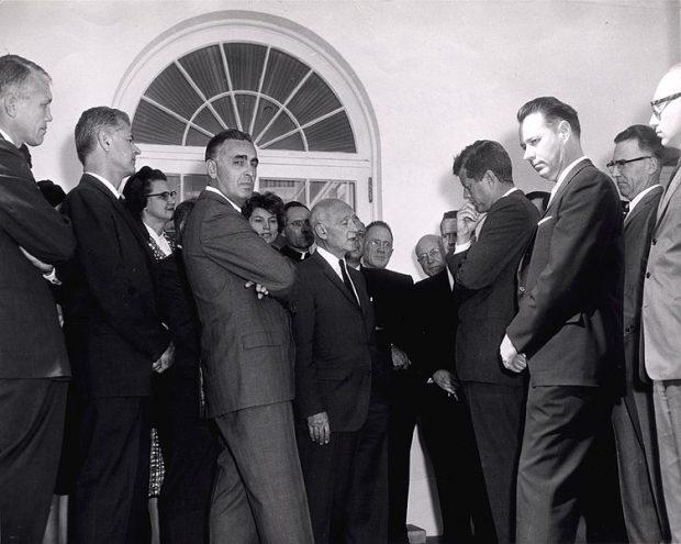 Casi oculto, Wendell Stanley asoma la cabeza al fondo de esta foto tomada en la Casa Blanca en 1961, durante un encuentro con científicos del presidente John F. Kennedy. Imagen de White House / Wikipedia.