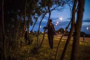 Un migrante espera para saltar una cerca antes de intentar tomar un tren en su ruta hacia Inglaterra, en Calais. (Francia) (EFE).