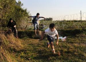 """Motasin, de 8 años, y su hermano Mutaz, de 11, corren tras pasar la frontera de Serbia con Hungría """"ilegalmente"""", junto con su madre Lama, en su camino hacia Alemania. / SERGI CÁMARA"""