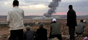 Varias personas observan el humo causado por una explosión contra integrantes de Estado Islámico en la ciudad siria de Kobani. (EFE / Sedat Suna)