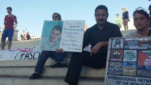 Shaker Kakaj durante una manifestación en la plaza Sintagma de Atenas con un cartel donde denuncia el presunto asesinato de su hijo / N.S.I.