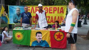 Rastim a la izquierda, junto a una imagen de Öcalan y un kurdo explicando su reivindicación a un griego en Sintagma / N.S.I.