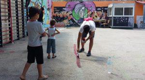 Unos niños de la escuela Quinta miran como un voluntario pinta en el suelo las líneas de una área de fúbtol / N.S.I.