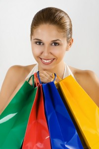 Woman holding bags. people woman young woman young 20-25 years one interior hold holding stand standing bags bag colourful colour smile smiling enjoy enjoying vertical shopping shop