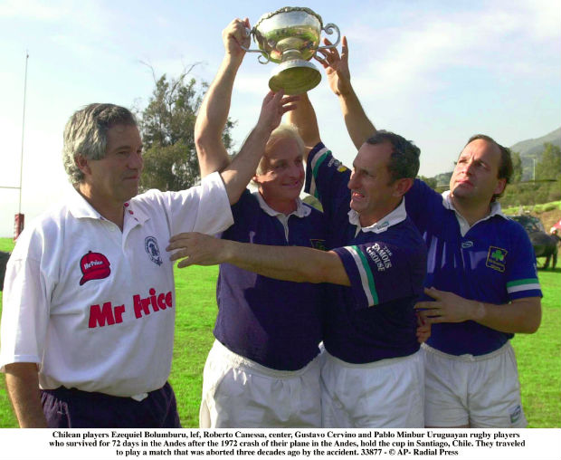 Chilean players Ezequiel Bolumburu, lef, Roberto Canessa, center, Gustavo Cervino and Pablo Minbur Uruguayan rugby players who survived for 72 days in the Andes after the 1972 crash of their plane in the Andes, hold the cup in Santiago, Chile, Saturday, Oct. 12, 2002. They traveled to play a match that was aborted three decades ago by the accident. (AP Photo/Santiago Llanquin. GTRES)