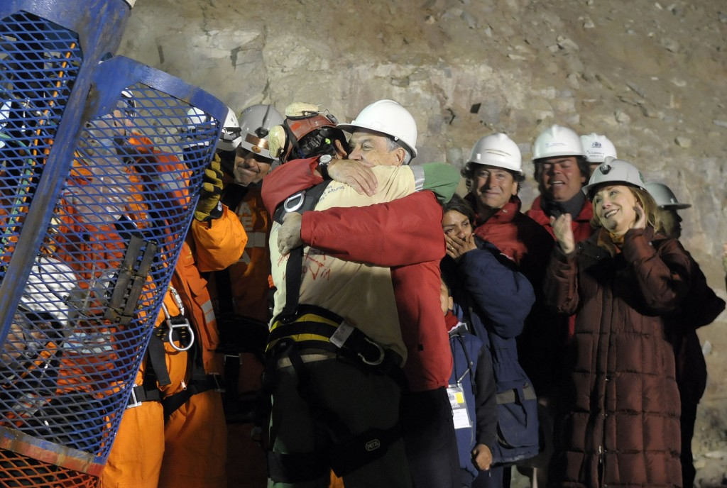 Florencio Avalos, the first miner to be rescued, left, is embraced by Chilean President Sebastian Piñera after his rescue in presence of his wife, his son, Chile's first lady and Mining Minister Laurence Golborne in San Jose mine, near Copiapo, Chile, on October 12, 2010.