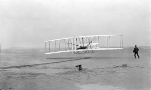 Fotografía original del primer vuelo con motor de la historia. A los mandos Orville Wright, a la derecha su hermano Wilbur (Wikipedia).