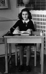 Anna Frank en un pupitre escribiendo.