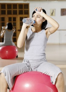 Young woman drinking water in the gym vertical people one young adult 20-25 years woman brunette exercise exercising train training interior gym work out sport ball sitting mirror tattoo tracksuit grey space hopper skippyball break rest resting keep fit fit health water mineral water bottle drink tired