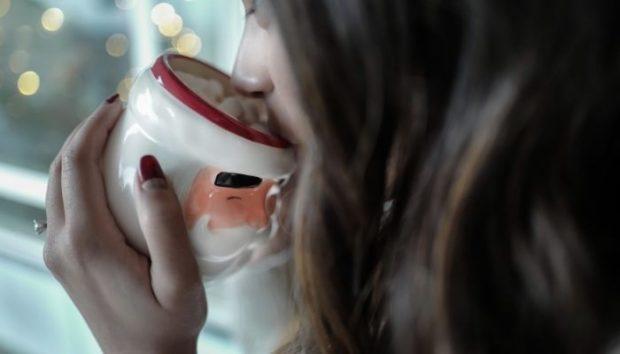Mujer bebiendo en taza navideña