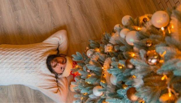 Hombre relajado al lado de árbol de Navidad