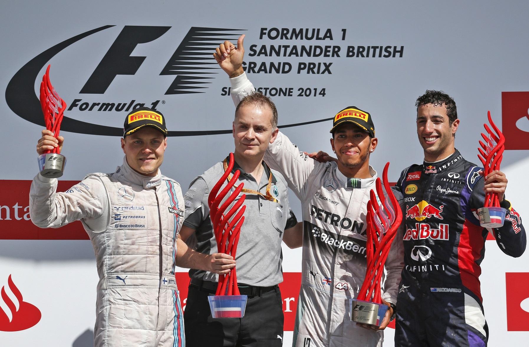 Valtteri Bottas, John Owen (del equipo Mercedes), Lewis Hamilton y Daniel Ricciardo, en el podio de Silverstone 2014 (GTRES).