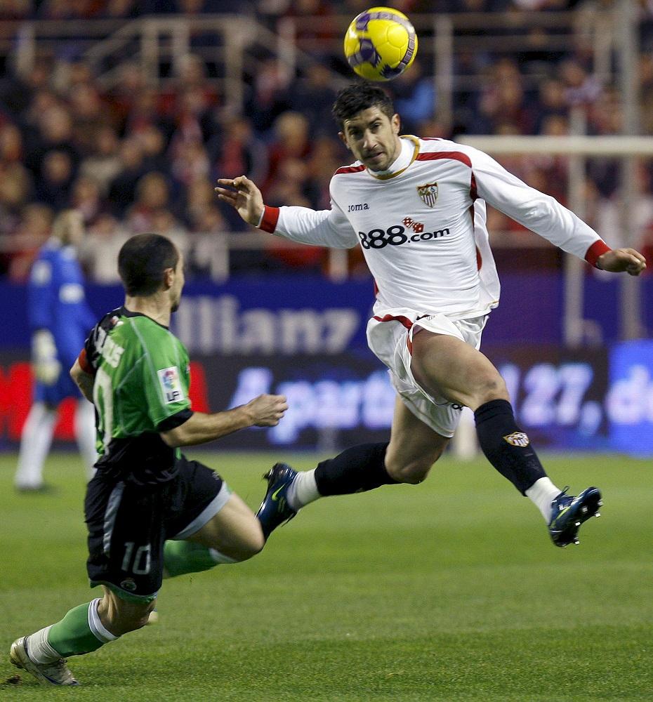 Dragutinovic despeja un balón frente al racinguista Munitis en un partido de Liga en el Pizjuán en enero de 2009 (Archivo 20minutos).