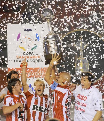 Verón alza la Libertadores de 2009. Obsérvese el abundante espacio en la peana para poner placas: era el primer año de la última versión del trofeo (WIKIPEDIA).