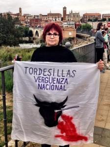 Una activista antitaurina muestra un trozo de sábana con un dibujo y una inscripción en contra del Toro de la Vega de Tordesillas. (JORGE PARÍS)