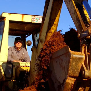 Manejando su querida excavadora.