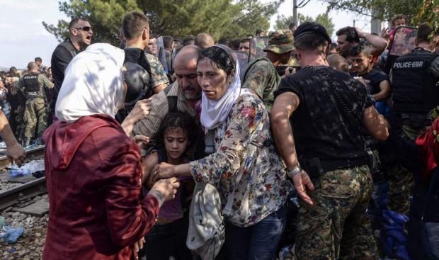 Refugiados tratan de de pasar a Macedonia por la frontera en tren con Grecia. (EFE)