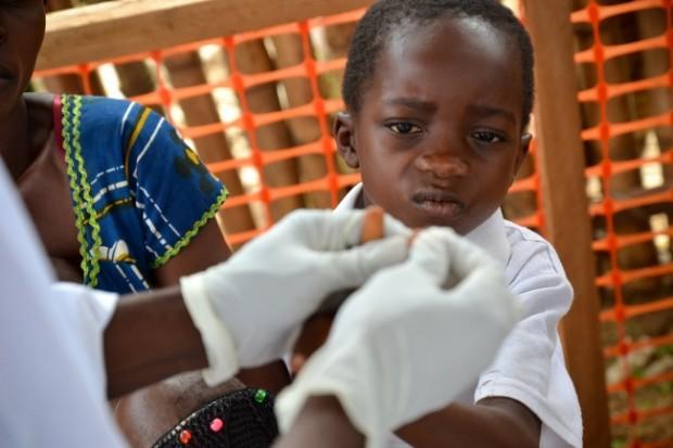 Una enfermera toma una muestra de sangre de un niño para realizar  un test rápido de malaria en el área de triaje del centro de salud de Bikenge. © Sandra Smiley/MSF