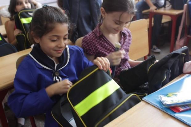 Una niña observa el contenido de su mochila fabricada en Siria ©UNICEF/Syria/2015/Razan Rashidi