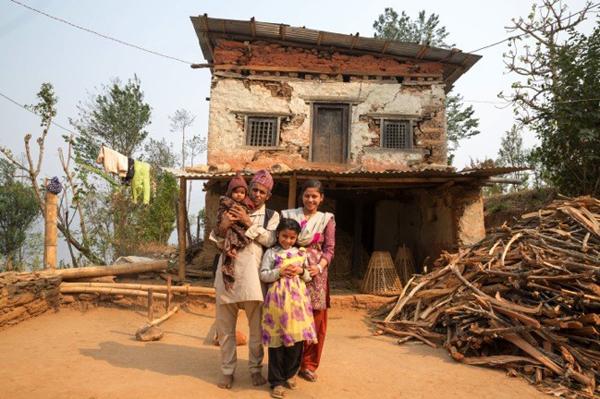 Shrijana y su familia posan frente a su casa, dañada por el terremoto de abril de 2015