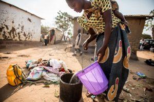 En su jardín, Martha vierte agua en un balde para lavar la ropa.