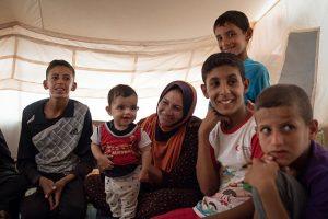 """© UNICEF/UN027628 Una familia que dejó hace poco su pueblo y llegó al campamento de Debaga se reúne en su tienda. Después de huir de su hogar la casa quedó destruida, pero Abu Omar, el padre, aseguró: """"Mi familia es lo más importante. Estamos a salvo. Eso es lo que importa""""."""
