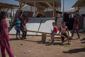 © UNICEF/UN027632/Mackenzie Unos niños juegan en un balancín improvisado en una de las nuevas extensiones del campamento para desplazados de Debaga, conocido como Debaga Dos.