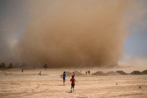 Foto 4 © UNICEF/UN025353/Mackenzie Unos niños corren hacia una tormenta de arena pasajera en un terreno que se está preparando para ser otra extensión del campamento para desplazados de Debaga, conocido como Debaga Dos.