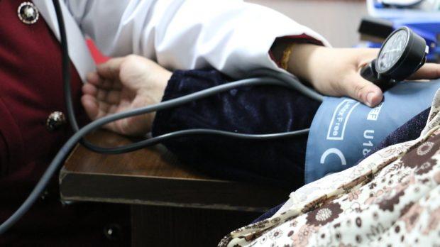 Majida es atendida en el hospital de MSF en Irbid mientras le toman la tensión. Fotografía: Maya Abu Ata/MSF