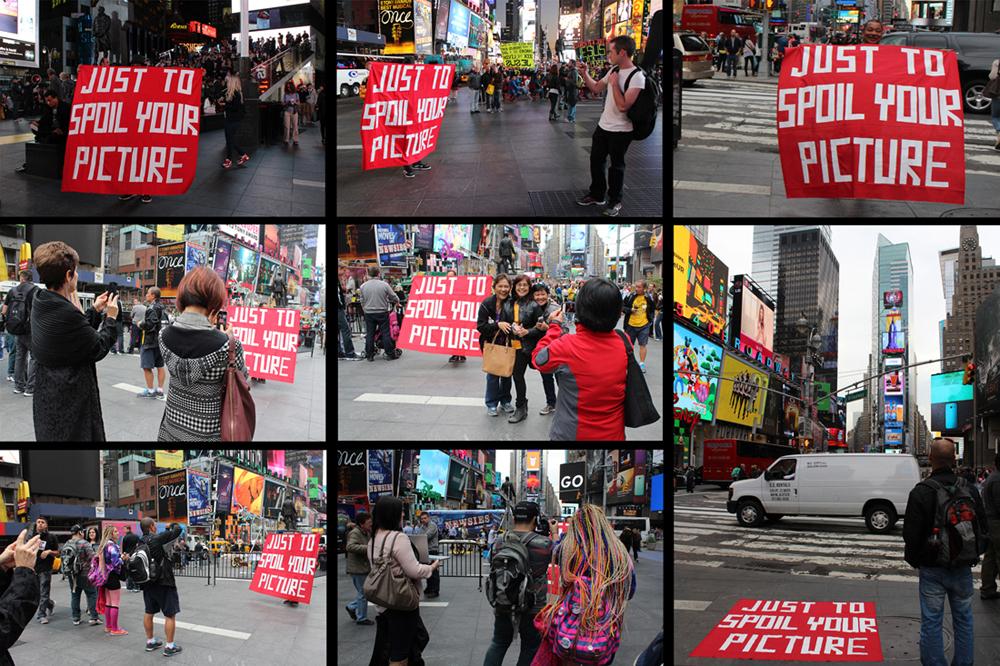 """'Disturbance - Times Square incursion'. Vlady sujeta un cartel en Times Square en Nueva York en el que se lee """"sólo para fastidiar tu foto"""" - Vlady - Foto: www.vladyart.com"""