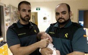 Foto del bebé abandonado en el contenedor en brazos de quienes le salvaron. (EFE)