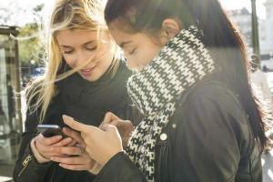Dos chicas mirando sus respectivos móviles (Gtres).
