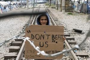 """Un niño refugiado afgano sostiene una pancarta en la que puede leerse """"no nos golpeen"""" (Georgi Licovski/EFE)."""