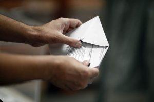 Una persona metiendo su papeleta en un sobre (Europa Press).
