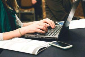 Una chica trabajando en un portátil (Infojobs).