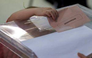 Una niña intentando meter una papeleta en la urna en las elecciones del 26-J (EFE).