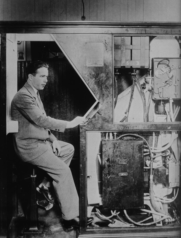 Anatole Josepho, inventor del fotomatón, con una de sus máquinas, a finales de los años veinte