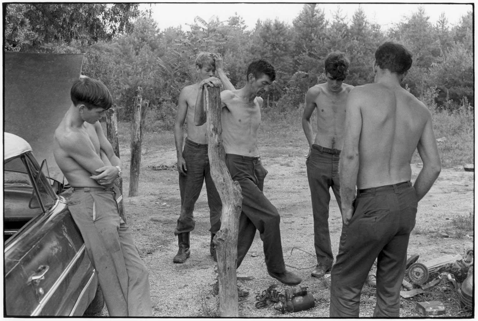 """Men without shirts; kicking car starter on the ground"" - William Gedney, 1972"