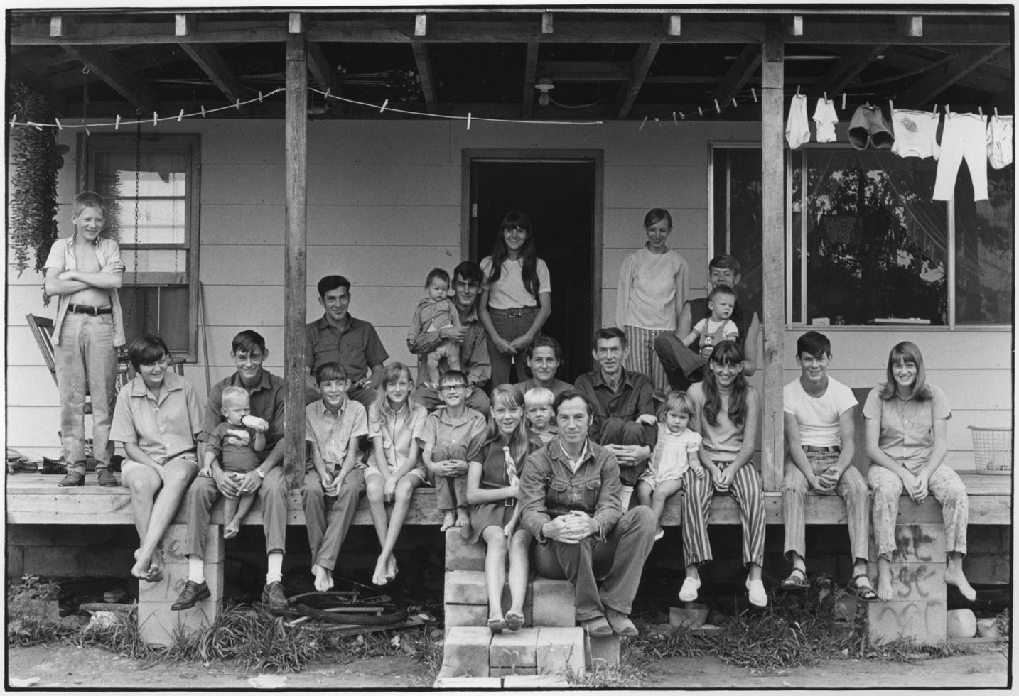 """Willie and Vivian Cornett, children and grandchildren, and William Gedney on porch"" - William Gedney, 1972"