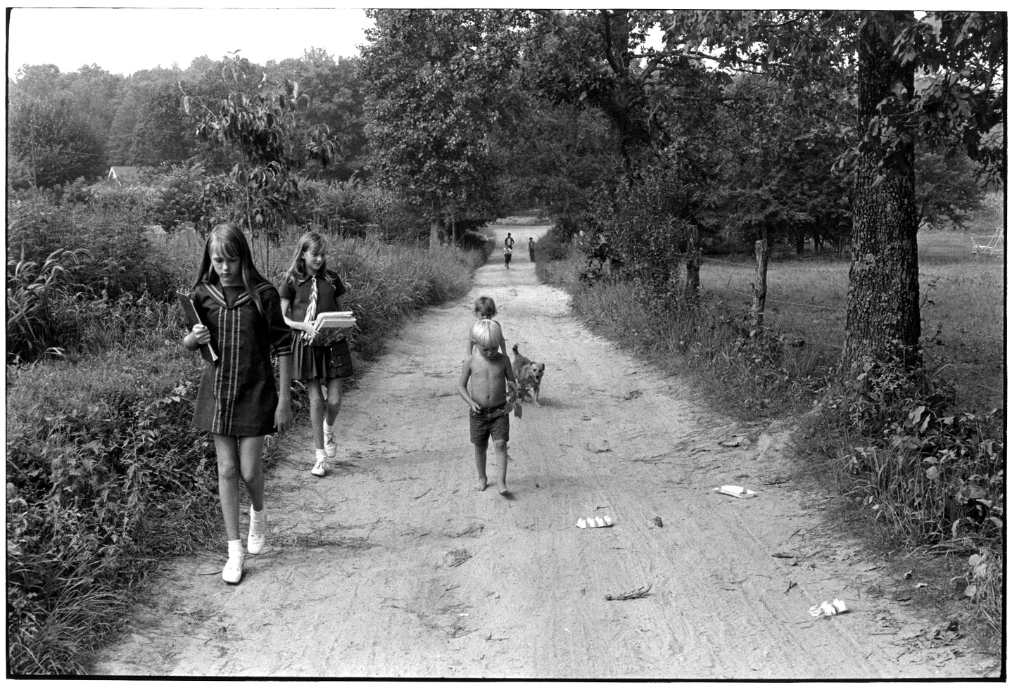 """Children and a dog walking on dirt road; two girls carrying books"" - William Gedney, 1972"