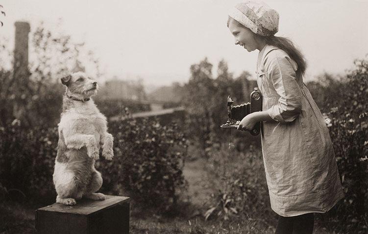 Una niña retrata a un perro con una Kodak de fuelle. Años veinte.